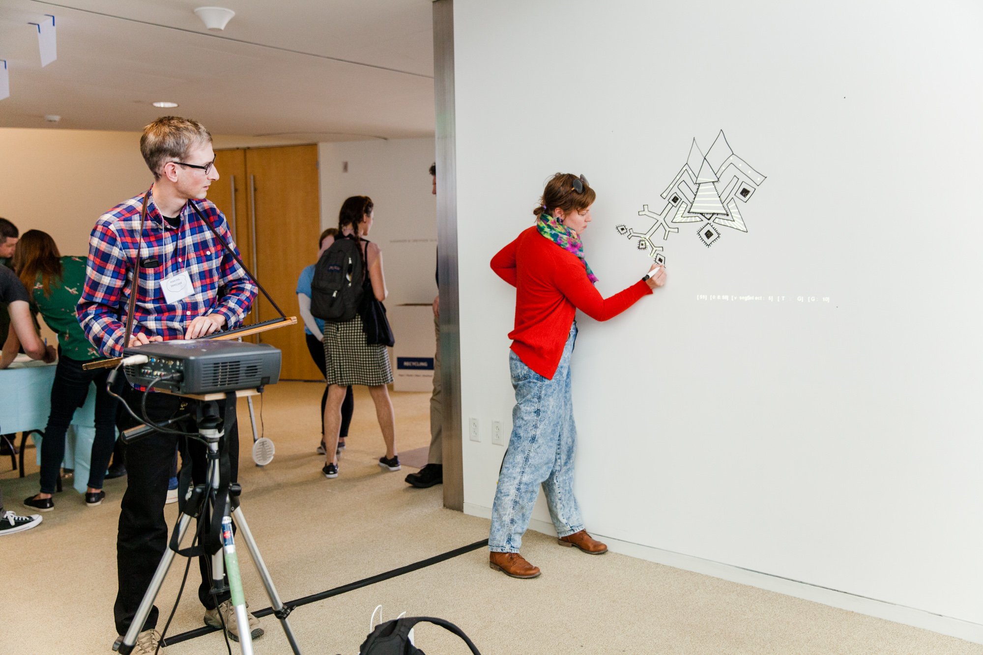 woman drawing art on the wall with man controlling projection with keyboard