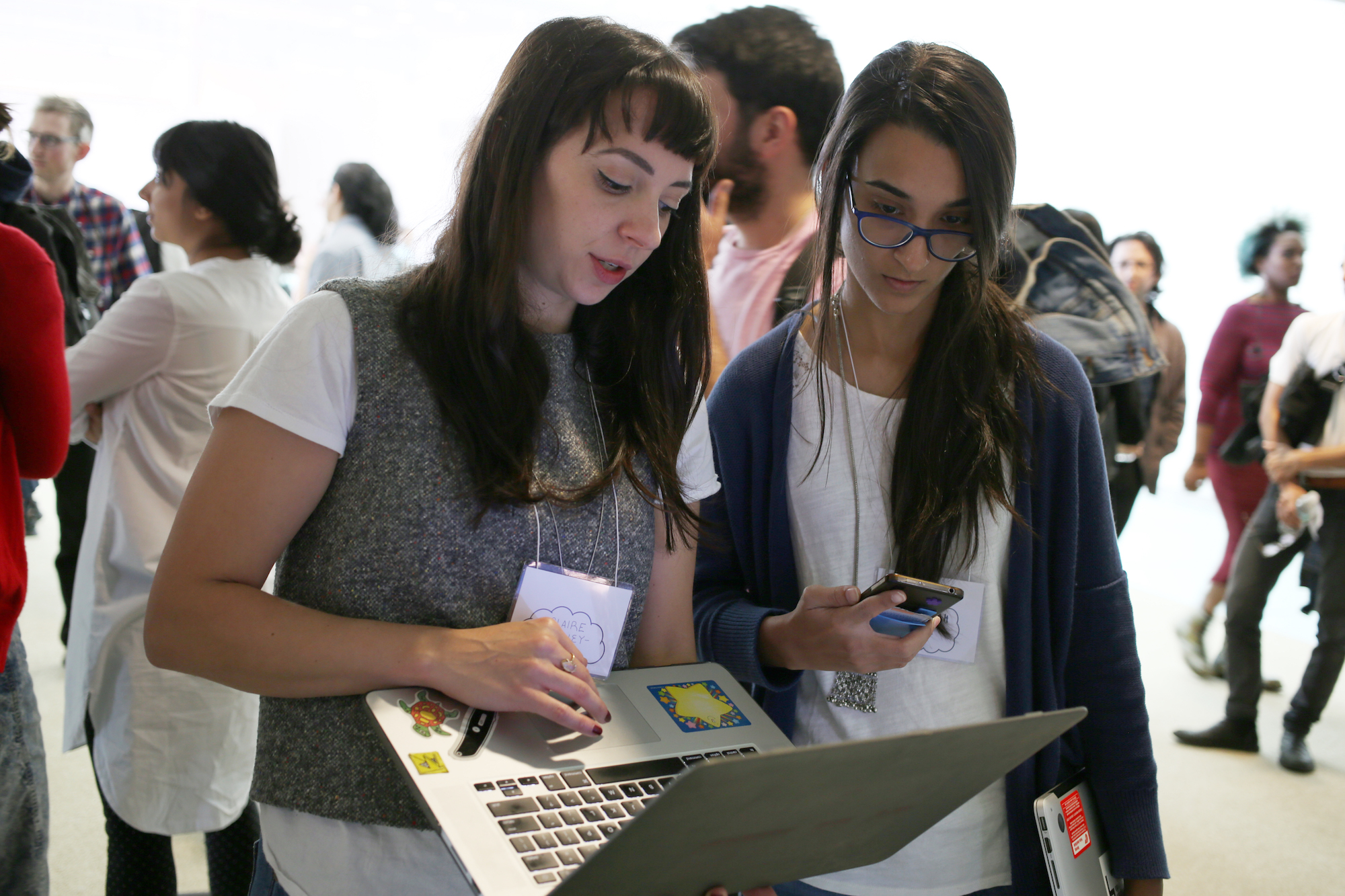 two women gathered around a computer